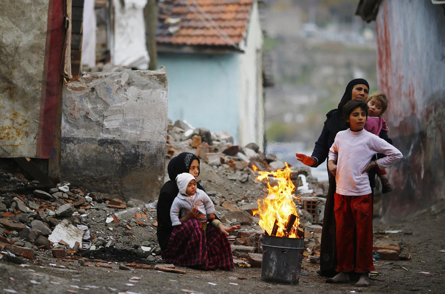 Syrian refugees warm themselves around fire in Turkey